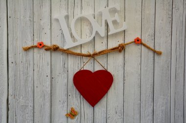 Red heart on white wooden wall with Love Lettering