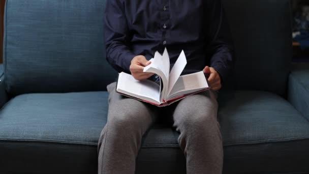 Fiatalember levelezik egy új iskolai könyvet a közgazdaságtanról és a különböző üzleti stratégiákról. Sóhajtson, hogy hány oldal van a könyvben. Videofelvétel Full HD 60 fps.