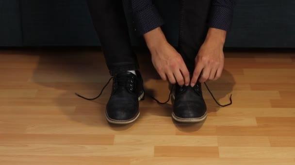 Demonstration, wie man seine Schuhe richtig bindet. Ein junger kreativer Mann zeigt den Kindern, wie man richtig eine Verbeugung an den Schuhen macht. Eine der grundlegenden und intuitiven Bewegungen. Videoaufnahmen Full HD 60 fps.