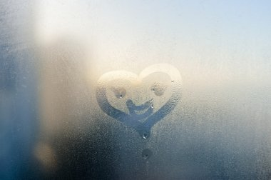 Smile face and heart drawing on window, season abstract background. Rain drops