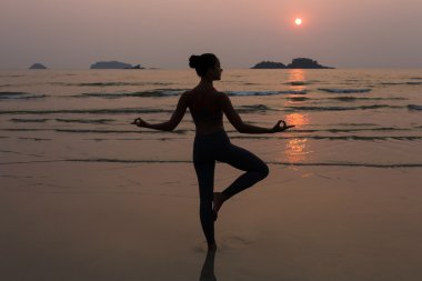 Young slim woman practicing pose from yoga on the beach at sunset