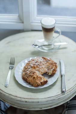 Delicious almond croissant on vintage white table with hot coffee latte