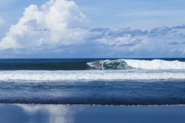 Surfer at the wave in Bali surfing spot