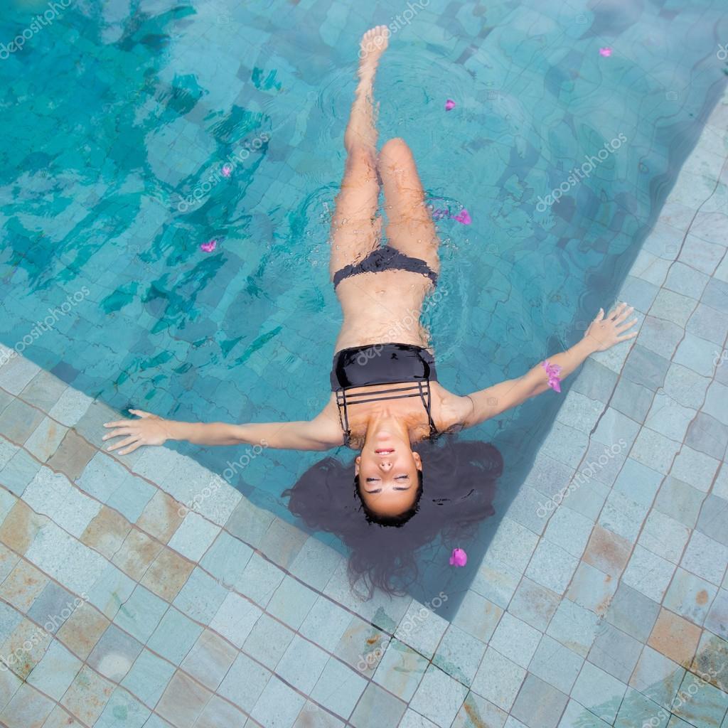 Hermosa mujer sexy disfrutando en la piscina de lujo en ...