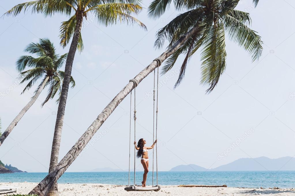 Woman swinging on on paradise beach
