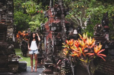 Young woman by an old Balinese architecture