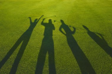 Four golfers silhouette on grass