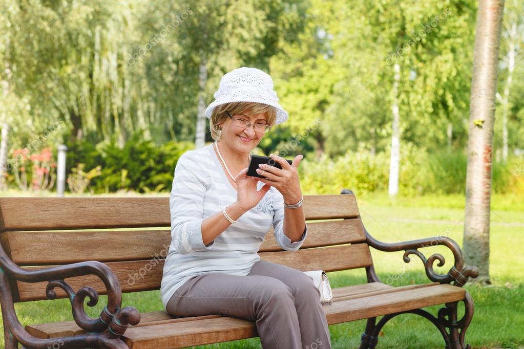 Attractive mature woman using smartphone in a park .– imagens de bancos de  imagens