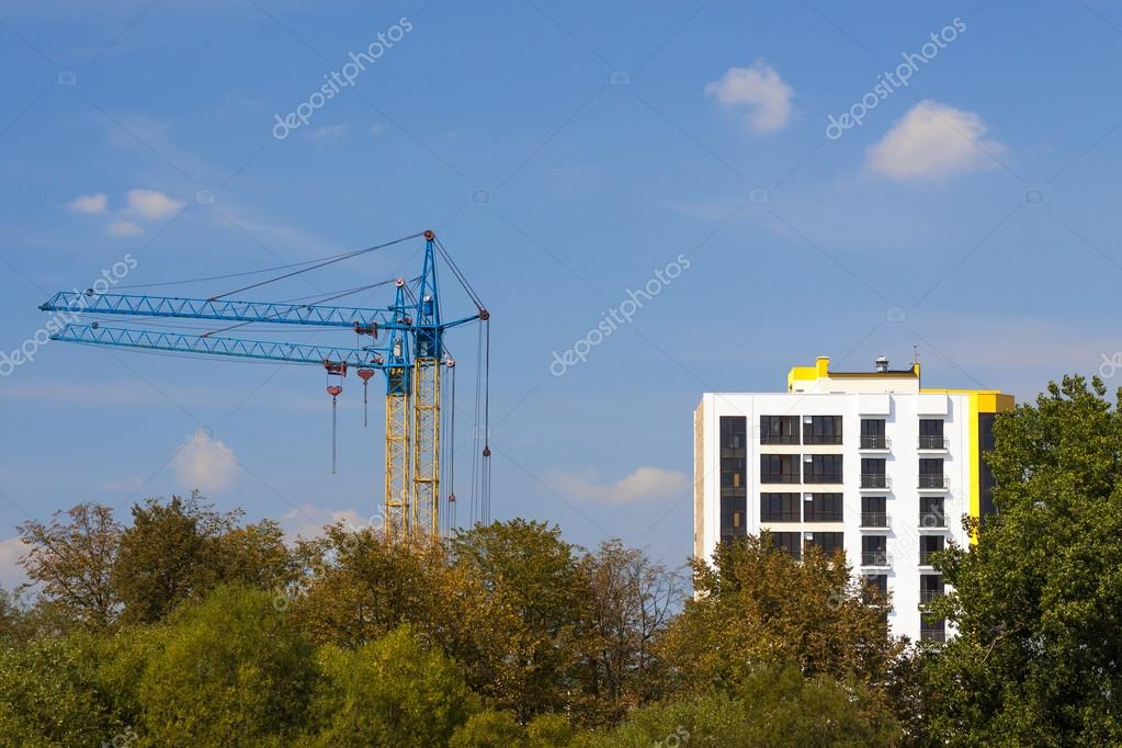 Tower cranes on a construction site near building and green tree