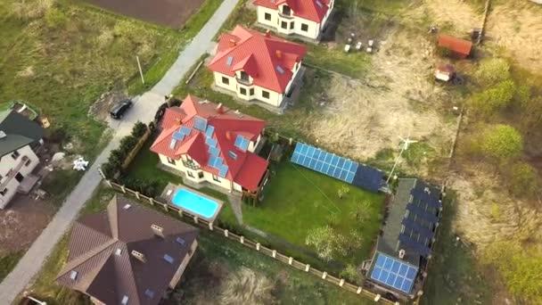 Luftaufnahme eines Privathauses mit begrüntem Rasen bedecktem Hof, Sonnenkollektoren auf dem Dach, Schwimmbad mit blauem Wasser und Windkraftgenerator.