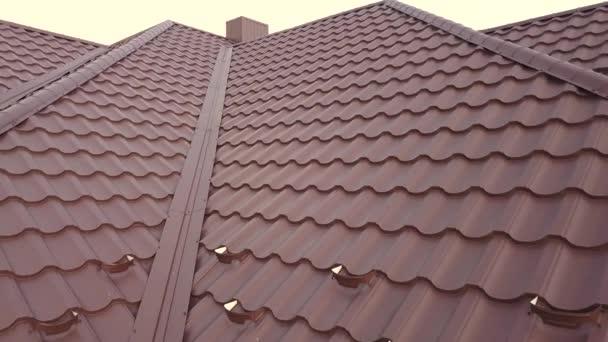 Letecký pohled na střešní konstrukci domu pokrytou kovovými dlaždicemi.