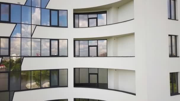 Mnoho oken na fasádě nového bytového domu.