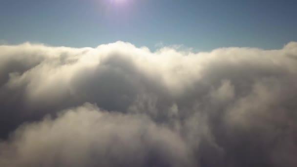 Letecký pohled shora na bílé opuchlé mraky v jasném slunečném dni.