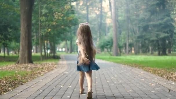Hátsó kilátás egy kislány nyári ruha séta egyedül a zöld parkban.