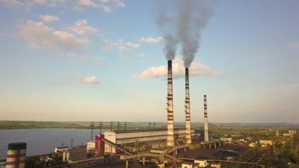 Letecký pohled na vysoké komínové trubky s šedým špinavým kouřem z uhelné elektrárny. Výroba elektřiny z fosilních paliv.