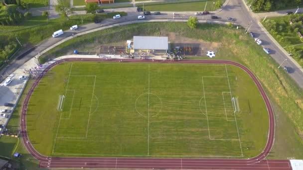 Légi felvétel egy futballpályáról egy stadionban, amelyet zöld fű borít a vidéki városrészben.