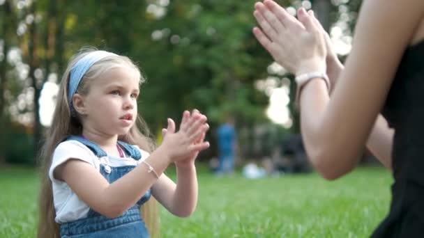 Hezké malé dítě dívka hrát hru se svou matkou s rukama venku v zeleném letním parku.