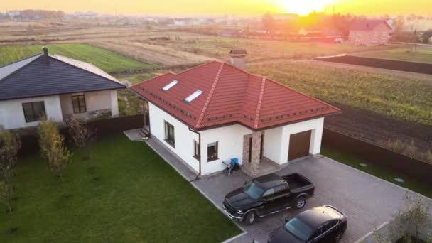 Luftaufnahme eines privaten Vororthauses mit geparkten Autos im Hinterhof.
