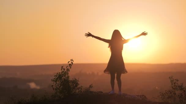 Tmavá silueta mladé ženy stojící se zdviženýma rukama na kameni a vychutnávající si výhled na západ slunce v létě.