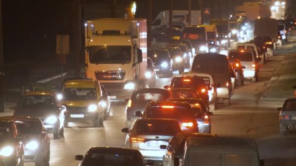 Dopravní zácpa s mnoha vozy pohybující se pomalu na ulici města v noci.
