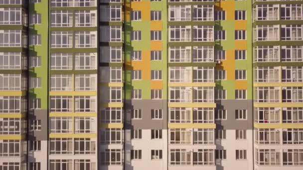 Letecký záznam vysokého bytového domu s mnoha okny a balkony.
