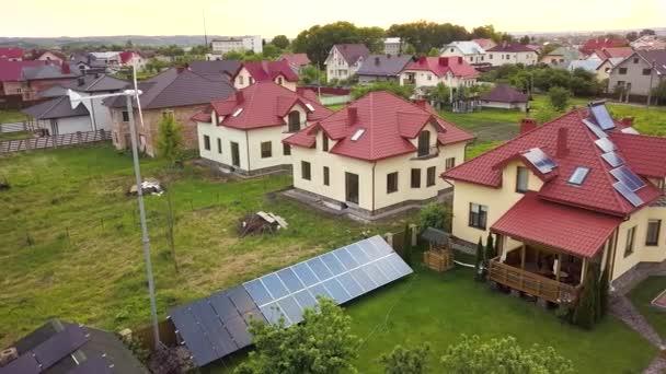 Luftaufnahme von Vororthäusern und Privathäusern mit begrüntem Rasen bedecktem Hof, Sonnenkollektoren auf dem Dach, Swimmingpool mit blauem Wasser und Windkraftgenerator.