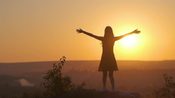 Mladá žena v letních šatech skákání ven s nataženými pažemi těší pohled na jasně žlutý západ slunce.