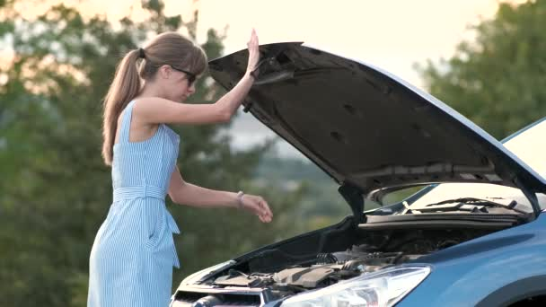 Puzzled young female driver standing near a broken car with open up hood inspecting her vehicle motor.