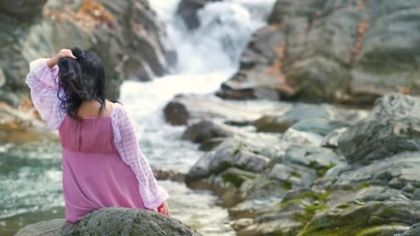 Žena v dlouhých módních večerních šatech sedí na kameni v blízkosti malé horské řeky s rychle tekoucí vodou.