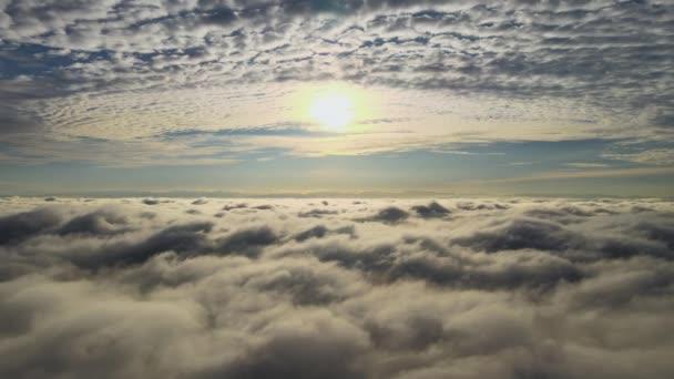 Vzdušný pohled na zářivě žlutý východ slunce nad bílými hustými mraky s modrou oblohou nad hlavou.