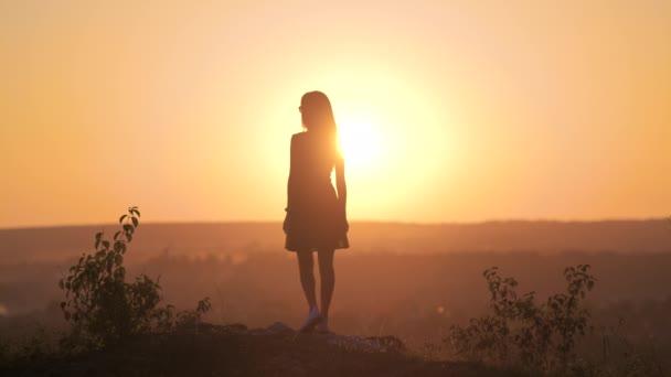 Tmavá silueta mladé ženy v letních šatech stojící venku těší pohled na přírodu při západu slunce.
