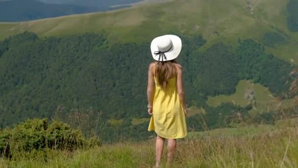 Rückansicht einer jungen glücklichen Reisenden in gelbem Kleid, die an einem windigen Tag in den sommerlichen Bergen auf einem grasbewachsenen Hang steht und mit ausgestreckten Armen die Aussicht auf die Natur genießt.