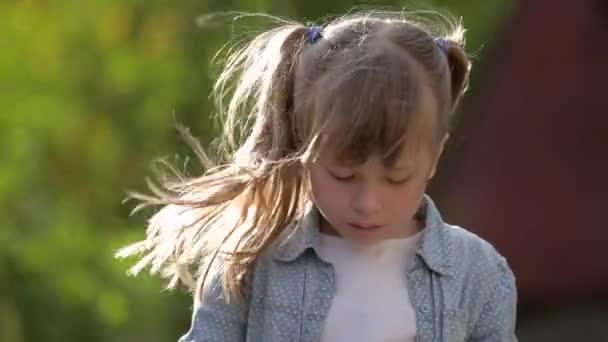 Dítě dívka jíst zmrzlinu s houbičkou venku.