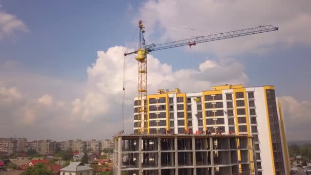 Stavební dělníci pracující na staveništi nové betonové obytné budovy.