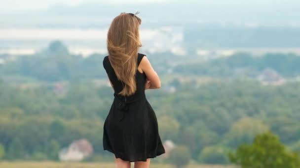 Dlouhé vlasy mladá žena v krátkých černých šatech stojící na vrcholu kopce těší teplé letní den.