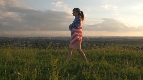 Back view of happy young woman running with USA national flag standing outdoors at sunset. Positive girl celebrating United States independence day. International day of democracy concept.