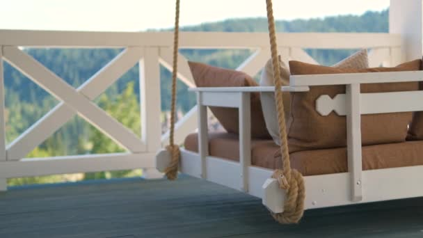 Close up of lightly swinging on summer wind comfortable couch swing on open outdoor terrace at suburban house.