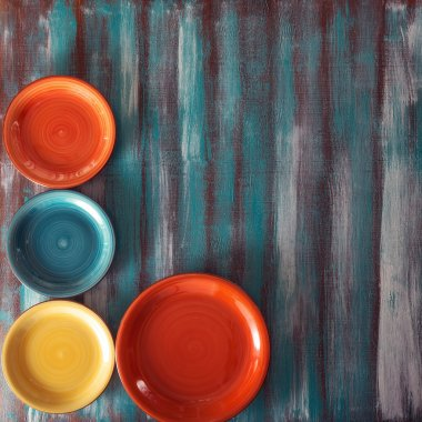 Colored plates on wooden background.