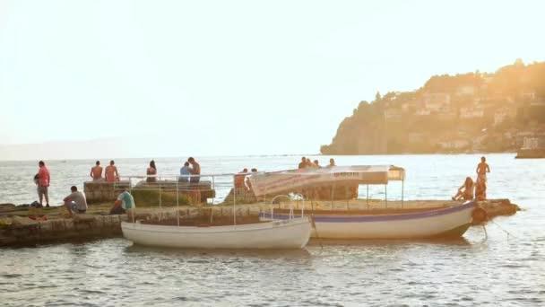 Ochrid, Makedonie, červen 2015: lidé, kteří se při západu slunce ochlazování u jezera Ochrid. Ochrid je proslulý historickým centrem na seznamu UNESCO a krásným jezerem oddělujícím Makedonii od Albánie.