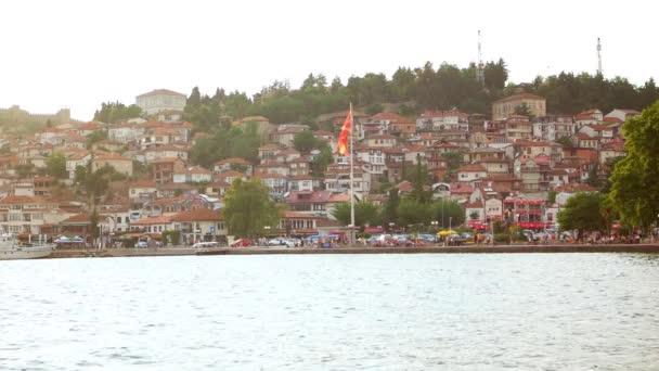 Ohrid, Makedonie, červen 2015: Pohled krásné přímořské město Ochrid a obrovská makedonská vlajka mávat z Ohridského jezera. Ohrid je známý pro jeho seznamu UNESCO historické centrum a krásné jezero