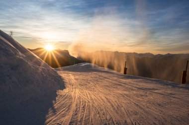 Skiers on the piste at dusk