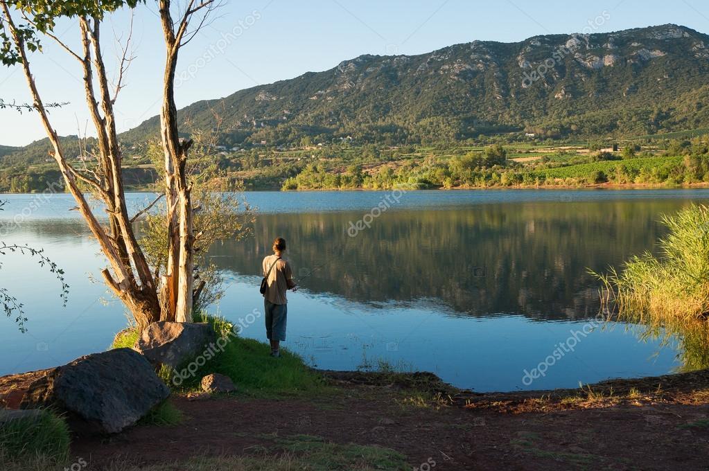 Une personne de pêche au bord du lac du Salagou ...