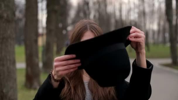 Mladá hezká holka v černém klobouku, který úsměvy šťastně do kamery, zblízka, zpomalené