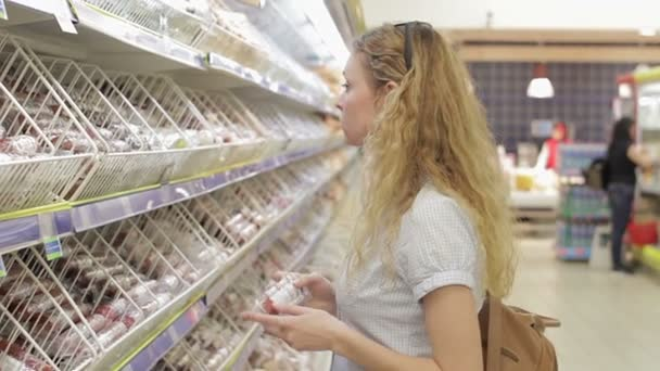 Mladá žena si vybere zboží v supermarketu