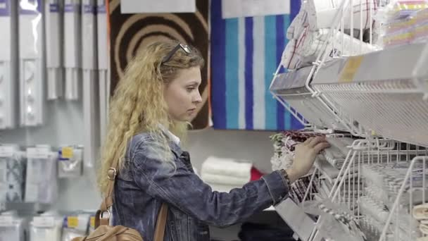 Mladá žena si vybírá Dětské zboží v supermarketu