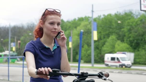 Fiatal nő a kerékpáros park mobiltelefonon beszél