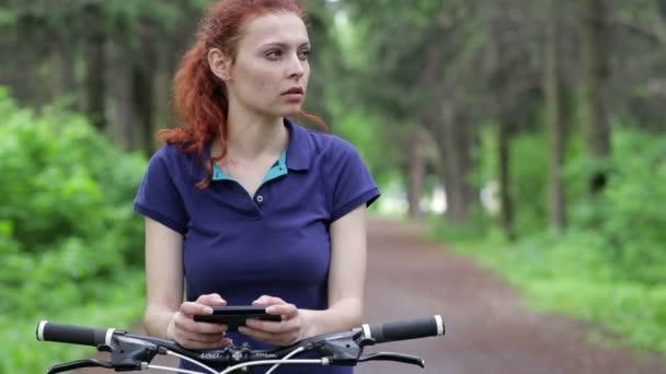 Žena využívání chytrý telefon a jízda na kole
