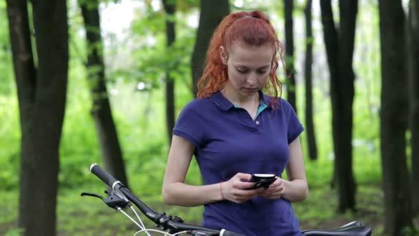 Dívka sedící na kolo a textových zpráv na smartphone
