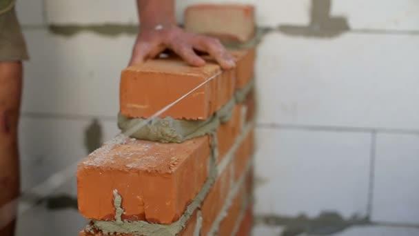 Práce klade cihly na staveništi