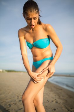Woman is testing the skin for stretch marks and cellulite on the beach.Woman holding/showing cellulite area.Self consciousness,self confidence and body insecurity